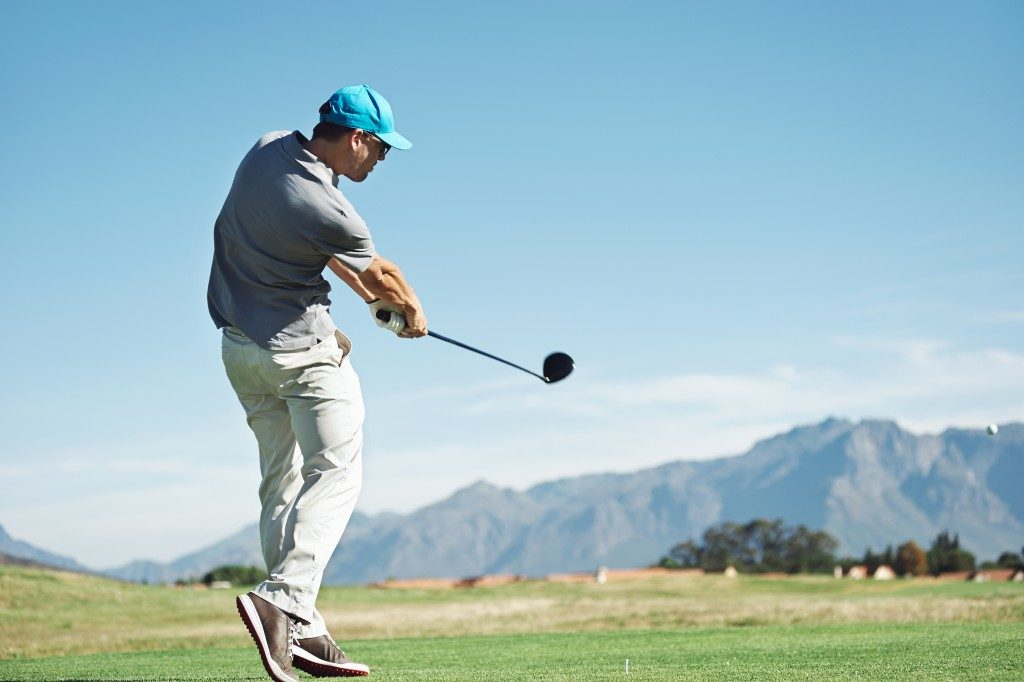 man in blue cap playing golf alone