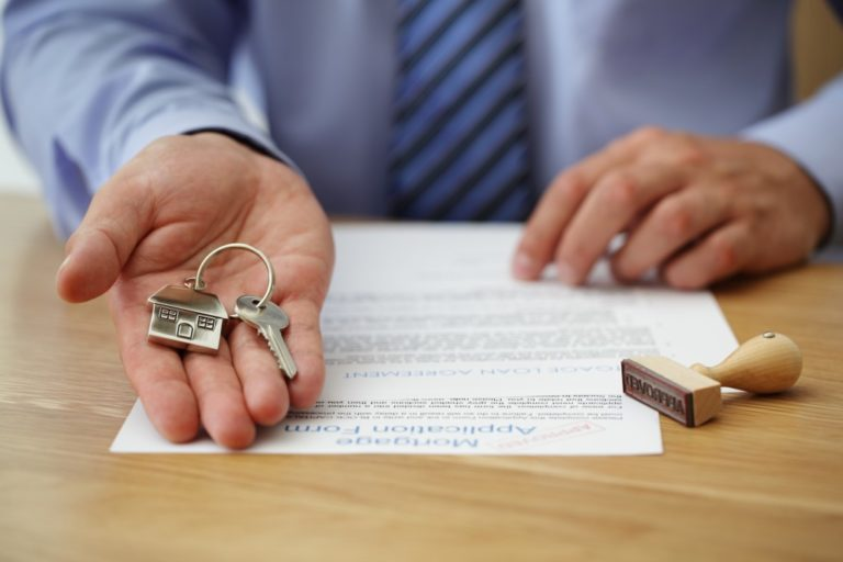 hand of real estate agent handing a home key